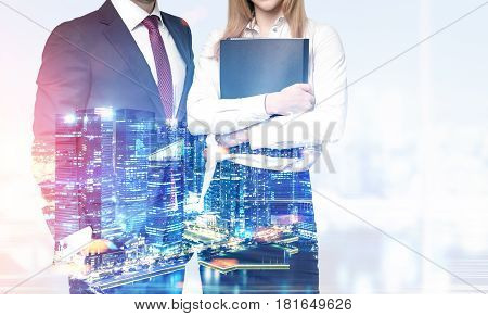Two unrecognizable business partners are standing together against a night city panorama. Toned image double exposure