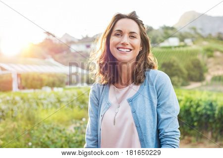 Cheerful mature woman enjoying in park during sunset. Happy hispanic woman in casual feeling relaxed outdoor. Smiling brunette woman looking at camera with carefree.
