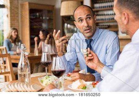 Business people meeting at restaurant. Mature businessman in a conversation with partner in restaurant. Senior employee in talking abouth the new agreement with his colleague during lunch.