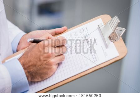 Close up of doctor hand filling medication list for a patient. Detail of hand of senior nurse complete the form of medicine. Doctor writing list of patient medicine in a hospital.
