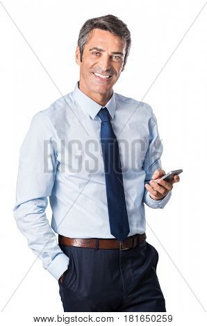 Relaxed mature business man typing message on smartphone and looking at camera. Portrait of a happy senior businessman using cell phone isolated on white background.