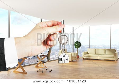 Hand holding key with house keychain in modern office interior with city view. Real estate concept. 3D Rendering