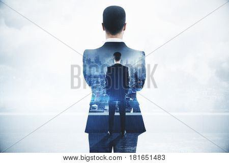 Back view of thoughtful young businessman on rooftop with city view. Employment concept. Double exposure