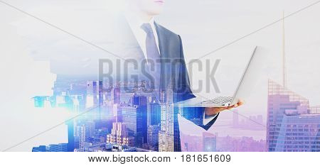 Side view of young businessman with laptop on abstract city background. Online business concept. Double exposure