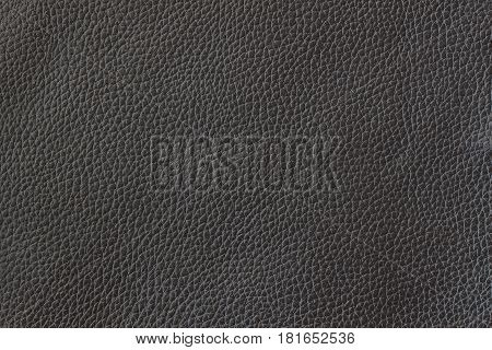 Texture of genuine leather close-up, cowhide. Black color. For natural, artisan backgrounds with copy space, substrate composition use, vintage design. Concept of shopping, manufacturing