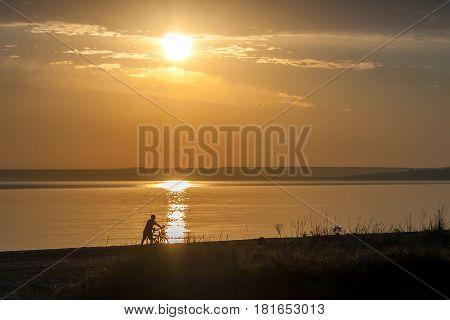 Beautiful colorful summer sea sunrise landscape with a blue sky and unrecognizable man with a bicycle silhouettes walking in the front of the Sun. In Crimea, Azov sea, Ukraine 2013.