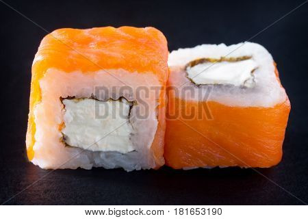 Roll Cheese Salmon Is Isolated On A Black Slate Board - Salmon, Soft Cheese, Nori, Rice.