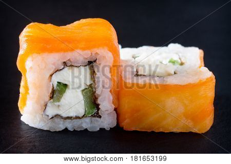 Roll Philadelphia Classic On A Black Slate Board - Salmon, Soft Cheese, Cucumber, Nori, Rice.
