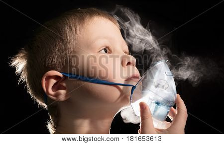 Kid breathing through nebulizer mask on black background