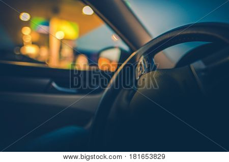 Car Driving Concept Photo. Vehicle Steering Wheel Closeup with Shallow Depth of Field. Gas Station Outside the Car Window.