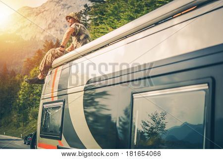 Caucasian Outdoor Man Enjoying the View From the Camper Van Roof. Motorhome Trip Concept.