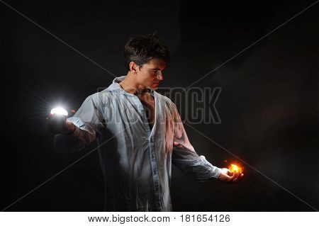 The sexy hot guy is holding a couple lights.