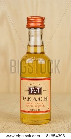 RIVER FALLS,WISCONSIN-APRIL 05,2017: A bottle of E&J brand peach brandy with a wood background.