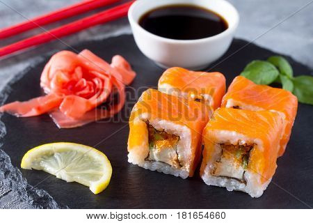 Roll Jamaica On A Black Slate Board - Tobiko Orange Salmon, Salmon, Soft Cheese, Cucumber, Nori, Ric