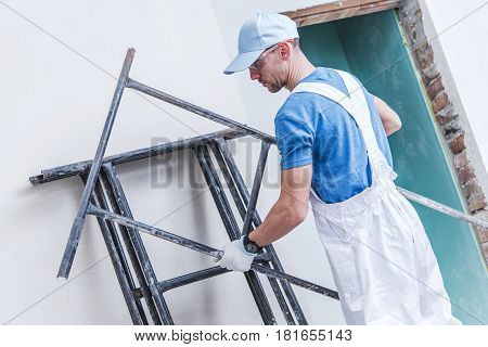 Caucasian Construction Worker Preparing Scaffolding Inside Remodeling House.