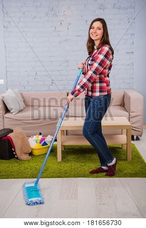 Young woman cleaner, dressed in casual clothes, washing wood floors, while in the room. household chores