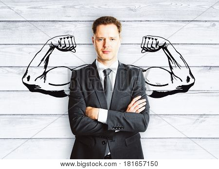 Confident businessman with drawn muscly hands on wooden background. Hero concept