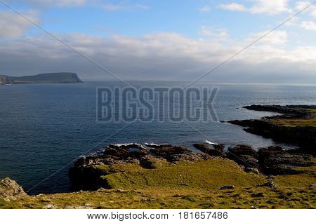 Rugged rock coastline with hills along the coastline.