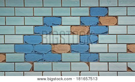 Partially destroyed blue tiles on the wall