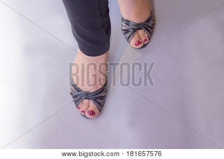 Woman dancing with salsa sandals. Nails painted red