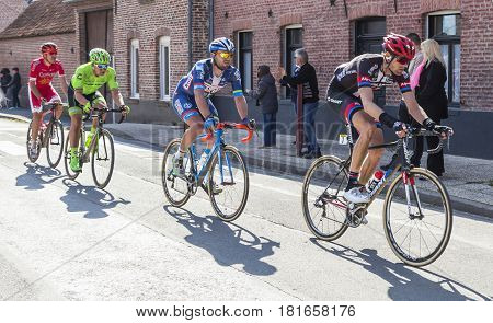 Louvil France - April 102016: Group of four cyclists riding in front of Louvil Town Hall in France during Paris Roubaix on 10 April 2016.