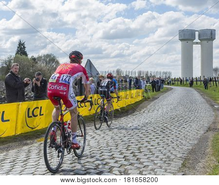 Hornaing France - April 102016: Two cyclists Kenneth Vanbilsen of Cofidis Team and Lars van der Haar of Team Giant-Alpecin riding on a paved road in Hornaing France during Paris Roubaix on 10 April 2016.