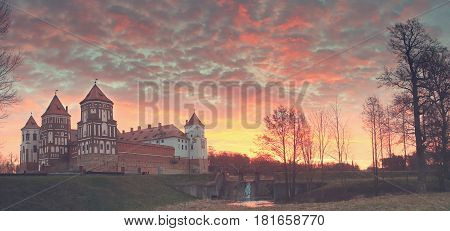 Landscape of the old castle against the background of dawn. Red clouds in the sky, a dam with a murmuring stream. The concept of antiquity. Mir Castle in Belarus.