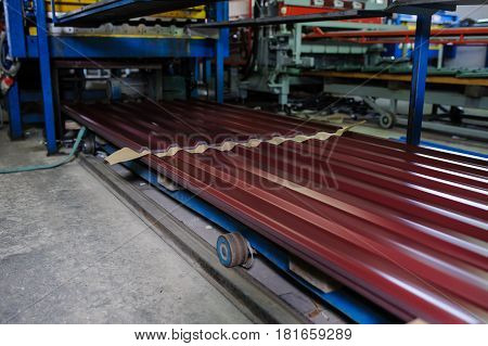 Metal tile manufacturing factory. Steel sheet metal roll profiling forming machine with rolls in working process.