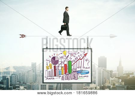 Businessman walking on abstract arrow with suspended business sketch. City background. Mock up. Profit concept