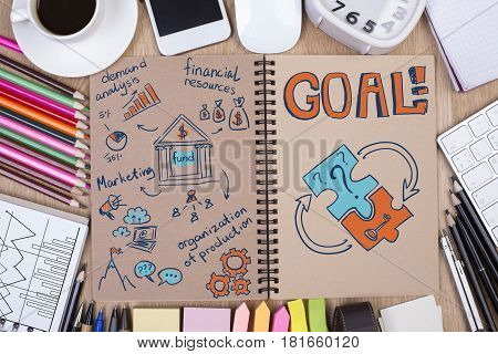 Top view of messy office desktop with sketch in notepad colorful supplies coffee cup electronic devices and other items. Goal concept