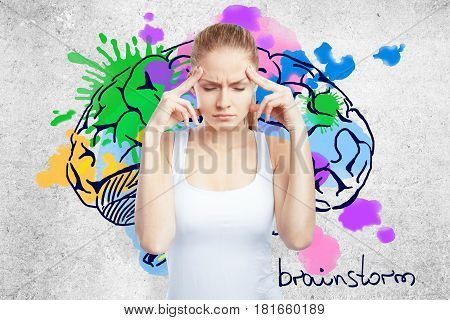 Pensive young european woman on concrete background with colorful brain sketch. Brainstorm concept