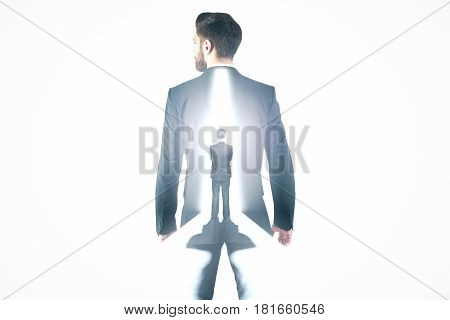 Back view of thoughtful businessman standing in front of open door with bright light. Opportunity concept. Double exposure