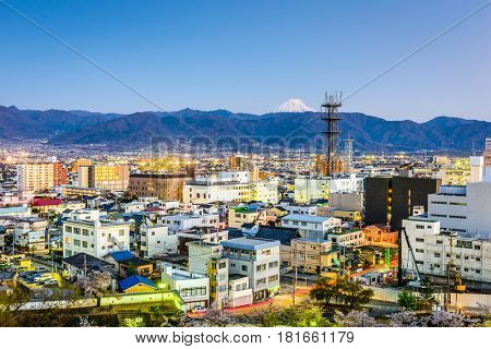 Kofu, Japan city skyline with Mt. Fuji peaking over the mountains.