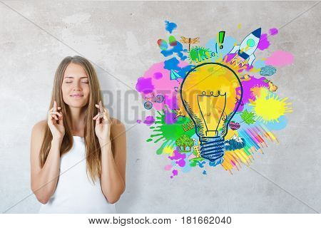 Happy young girl with crossed fingers on concrete background with lamp sketch. Successful startup ideas
