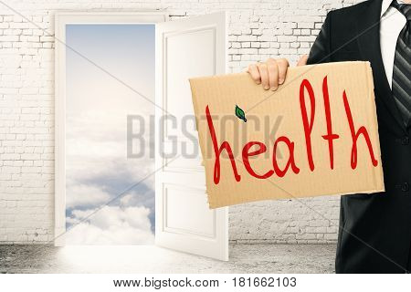 Businessman holding cardboard poster with health text in abstract interior with brick wall and door leading to heaven. 3D Rendering