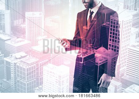 Side view of businessman using smartphone on city background with copy space. Communication concept. Double exposure