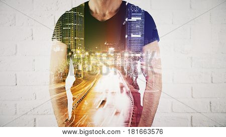 Guy on white brick background with abstract night city in motion. Double exposure