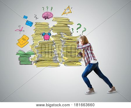 Casual european girl pushing drawn paper stacks on grey background. Workload concept