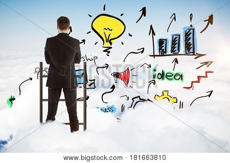 Back view of young businessman standing on top of ladder and looking at creative colorful sketch on sky background. Success concept