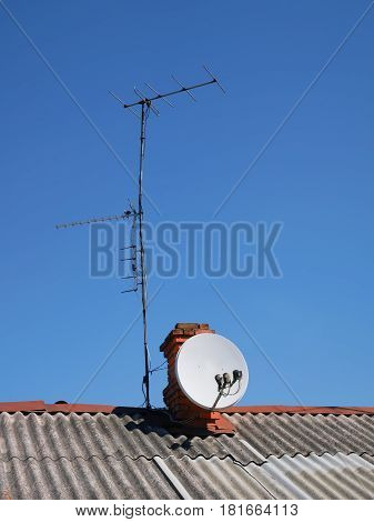Satellite TV and several terrestrial antennas installed on the slate roof of an old house on the background of a cloudless blue sky
