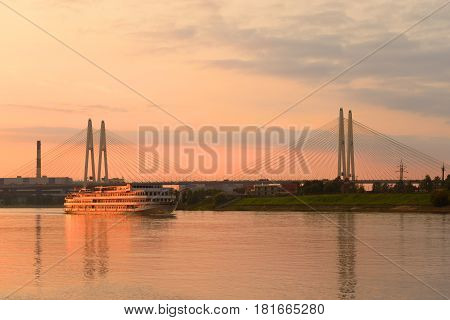 Cable-stayed bridge and river cruise ship at sunset in St.Petersburg Russia.