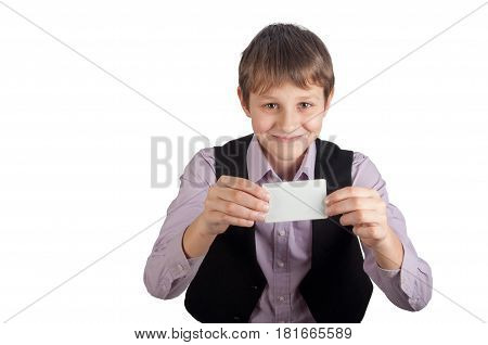 Smiling teenager in purple shirt and black waistcoat holding empty white card in hands. Isolated on white
