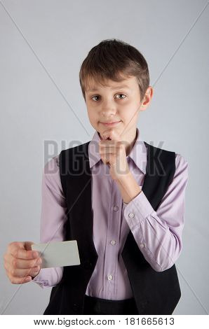 Thinking kid in purple shirt and black waistcoat holding credit card and hand on his chin on grey background. Vertical photo