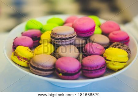 Beautiful multicolored decorated candy table baked sweet tasty cupcake cupcakes on a party with happy people around, beautifully decorated catering banquet table with different candy sweet delicacy