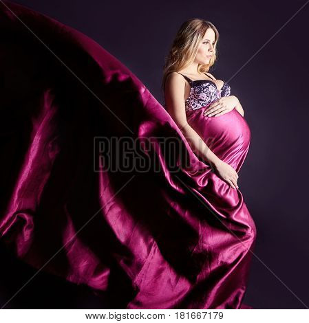 Pregnant woman in lingerie on gray background. A few days before birth. Beautiful pregnant blonde woman waiting for the birth of the child. Expectant mother