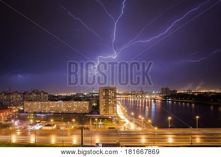 Lightning strikes in the city seen through the window, thunder in the night, thunderstruck over the cityscape