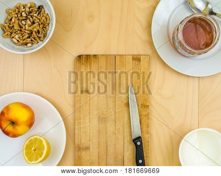 Four ingredients for a healthy and nutritious snack or smoothie, around board and knife, apple lemon fruit, cottage cheese, honey , shelled nuts walnuts, on plates from top view, arranged on wooden table in soft colours with copy space in the middle