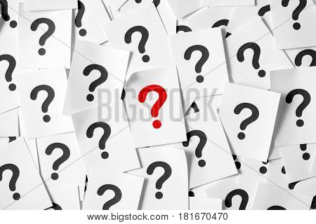 Pile of question marks written on papers forming background