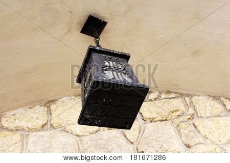 Old lantern near the wall of stone