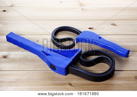 Two Strap Wrenches on a Wooden Background